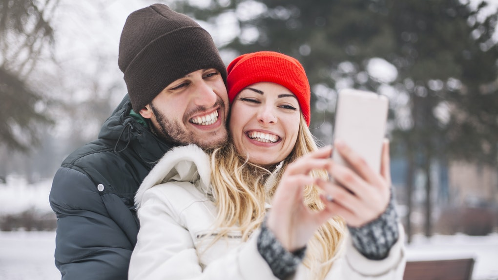 Happy couple taking selfie by smart phone in winter