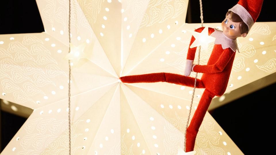an elf on the shelf doll on a star-shaped light