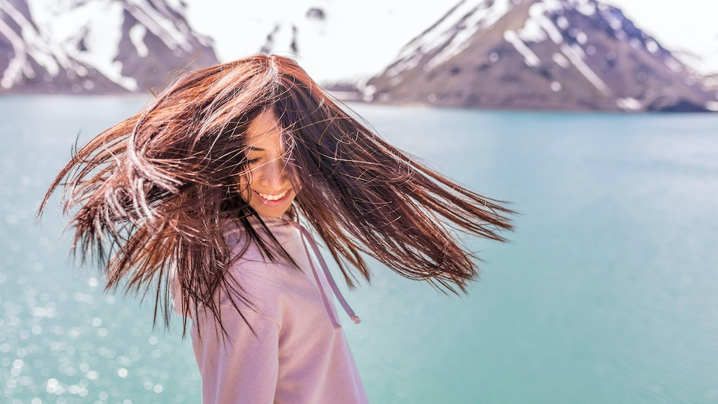 "Girl looking at the amazing mountain view. with messy windy hair Turquoise waters of ""Embalse del Yeso"" (Cast Lake) at Santiago de Chile city in Andes mountains. Snow mountains and water reflections"