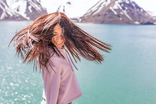 """Girl looking at the amazing mountain view. with messy windy hair Turquoise waters of """"Embalse del Yeso"""" (Cast Lake) at Santiago de Chile city in Andes mountains. Snow mountains and water reflections"""