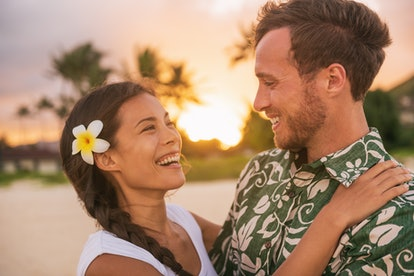 Happy couple lovers in love on romantic sunset beach vacation in Hawaii travel. Asian woman hugging ...