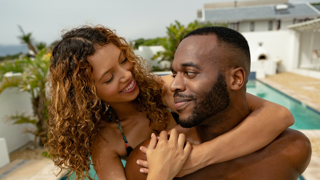 Close-up of African-american man giving piggyback ride to woman near swimming pool at the backyard of home. Summer fun at home by the swimming pool