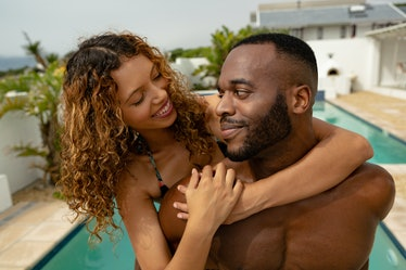 Close-up of African-american man giving piggyback ride to woman near swimming pool at the backyard o...