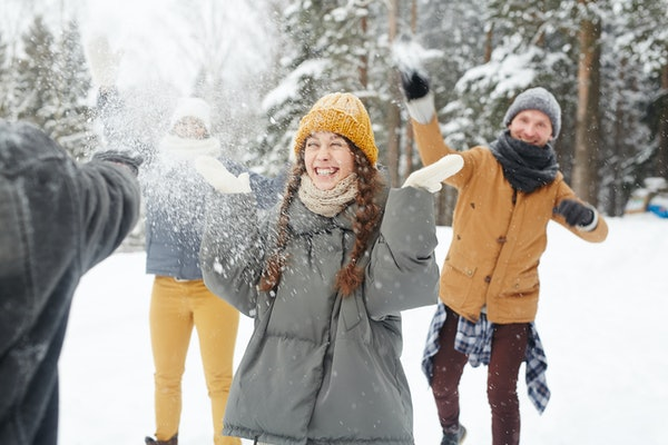 A smiling girl stands in the center of her friends in winter coats while they throw snowballs at her.