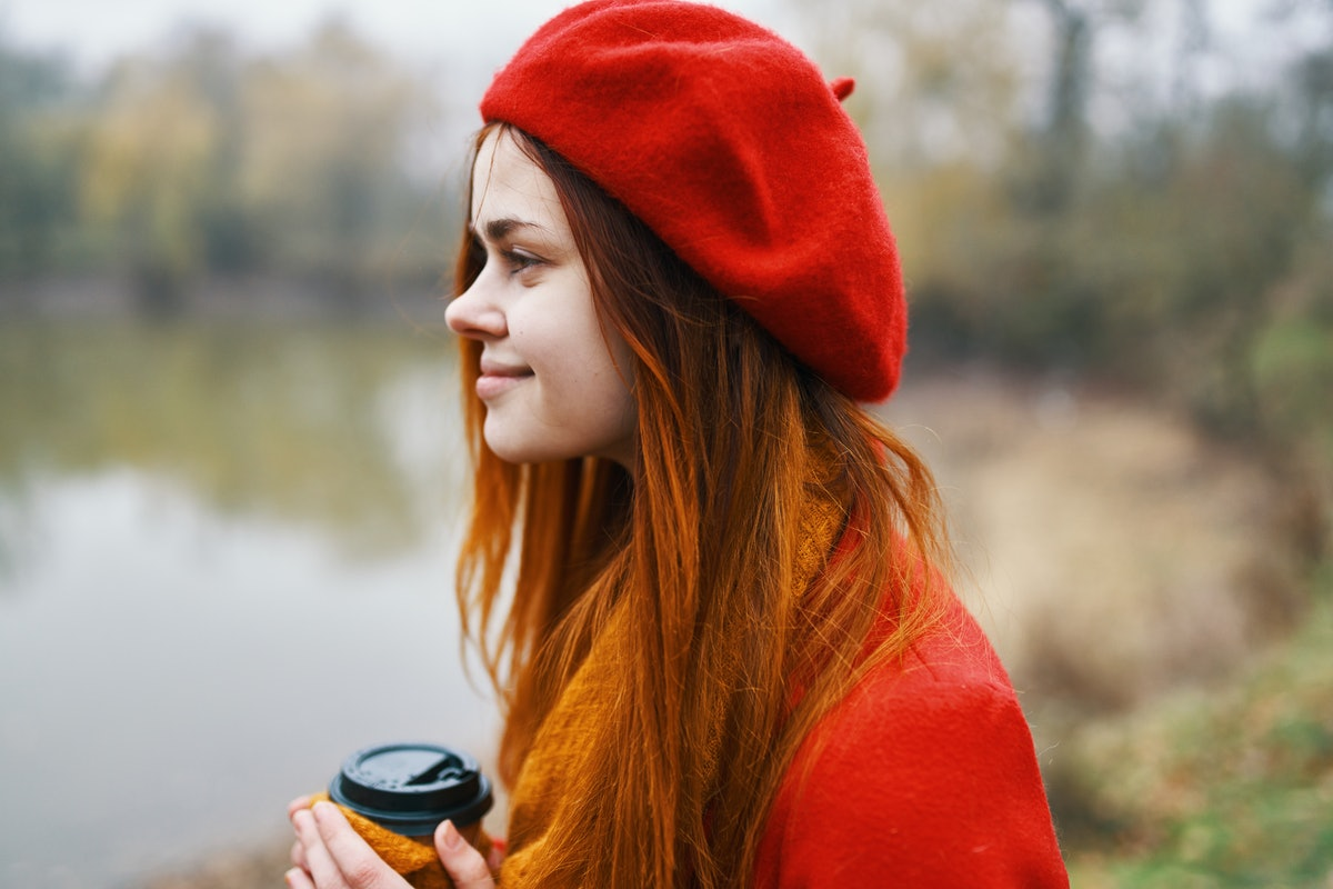 woman with coffee by the lake park silence