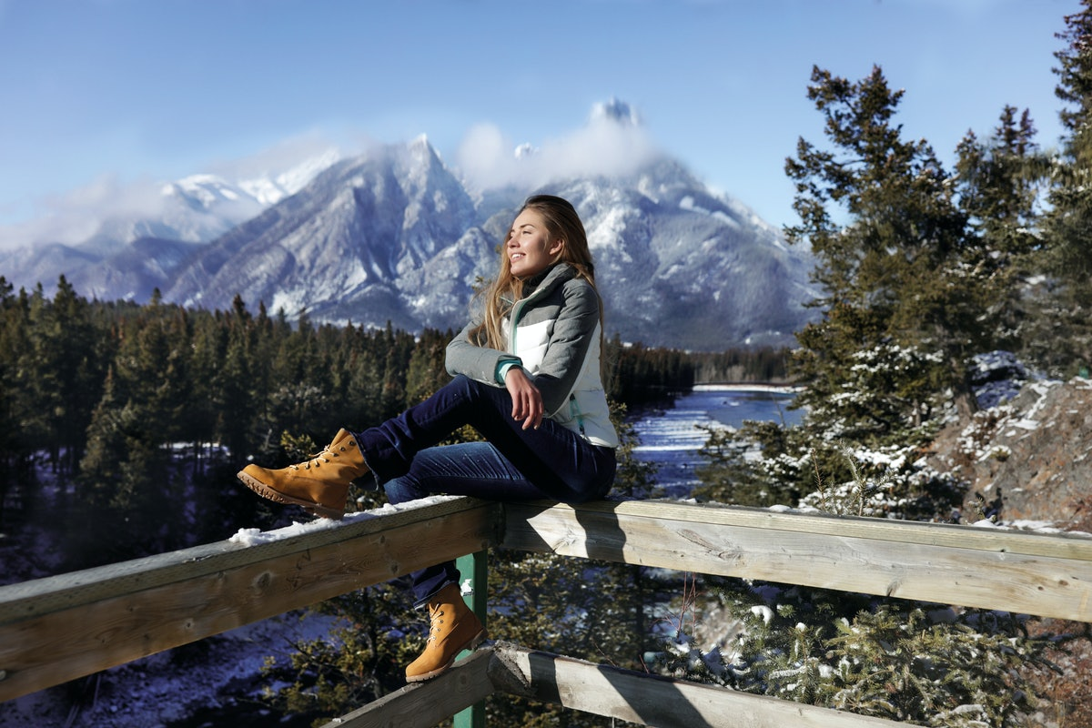 Sports girl sitting on a wooden fence, wearing sportswear, jeans and boots. Cold winter weather in C...