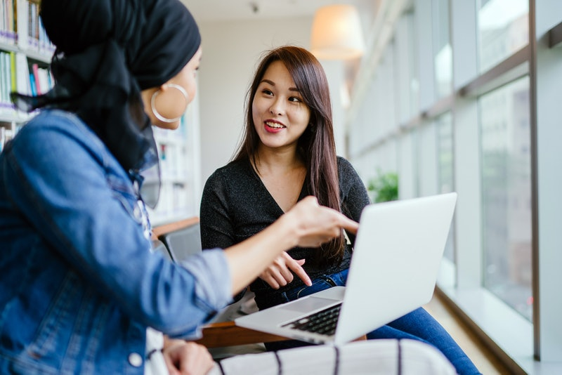 A young and attractive Chinese Asian woman has a business meeting with a Malay Muslim woman. They ar...