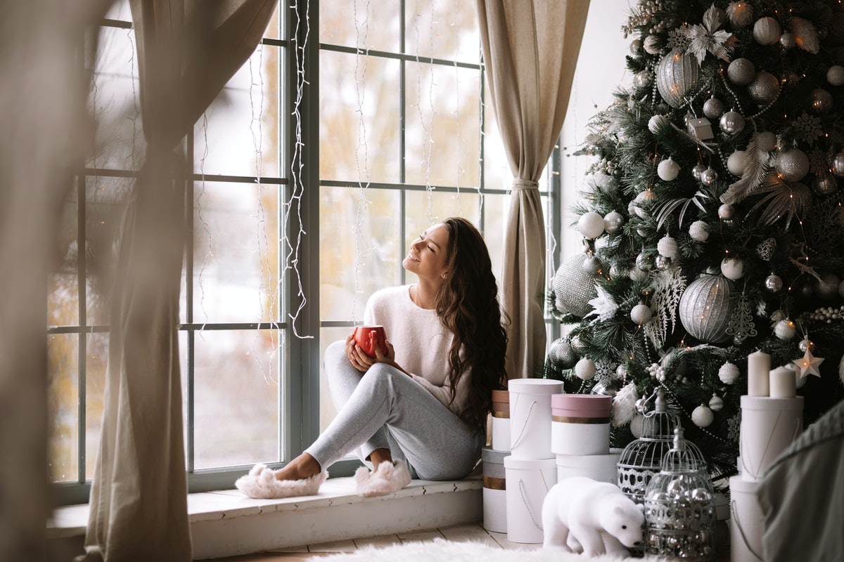Charming dark-haired girl dressed in pants, sweater and warm slippers holds a red cup sitting on the...