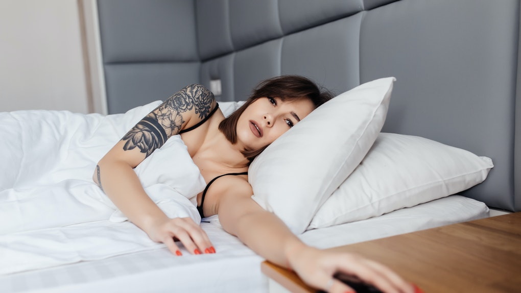 hand of woman turn off alarm on call mobile phone while wake up after sleep relax in good morning at bedroom.