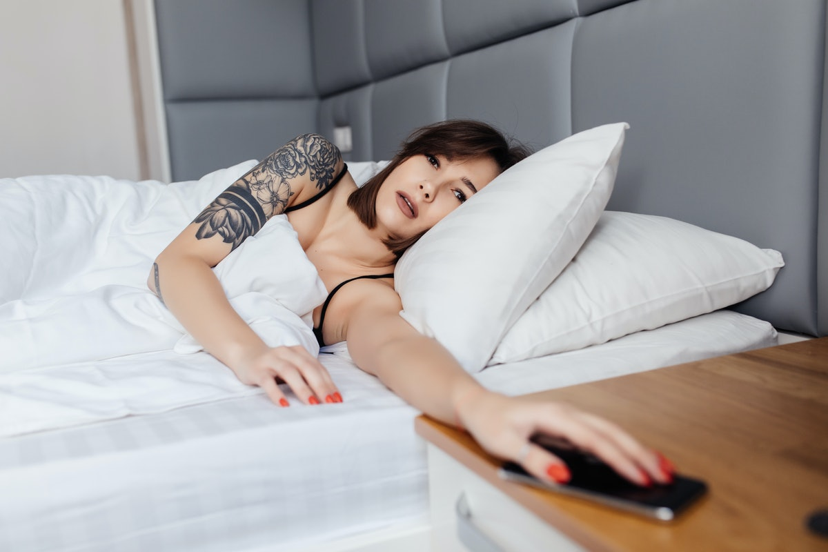 hand of woman turn off alarm on call mobile phone while wake up after sleep relax in good morning at...