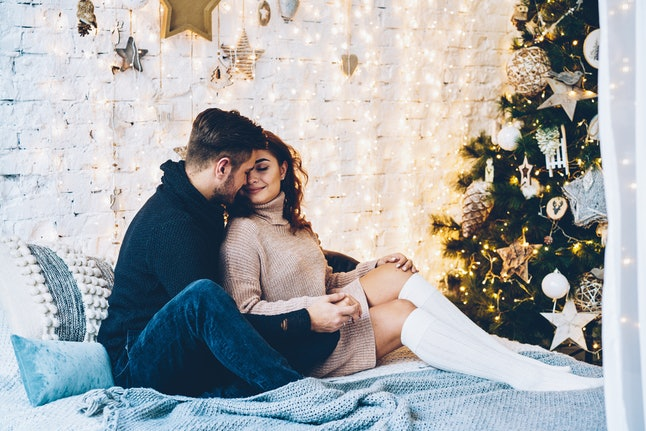 Young woman feeling joy and happiness in hugs f her handsome boyfriend spending winter vacations together. romantic family enjoying celebration Christmas together at cozy home with traditional tree