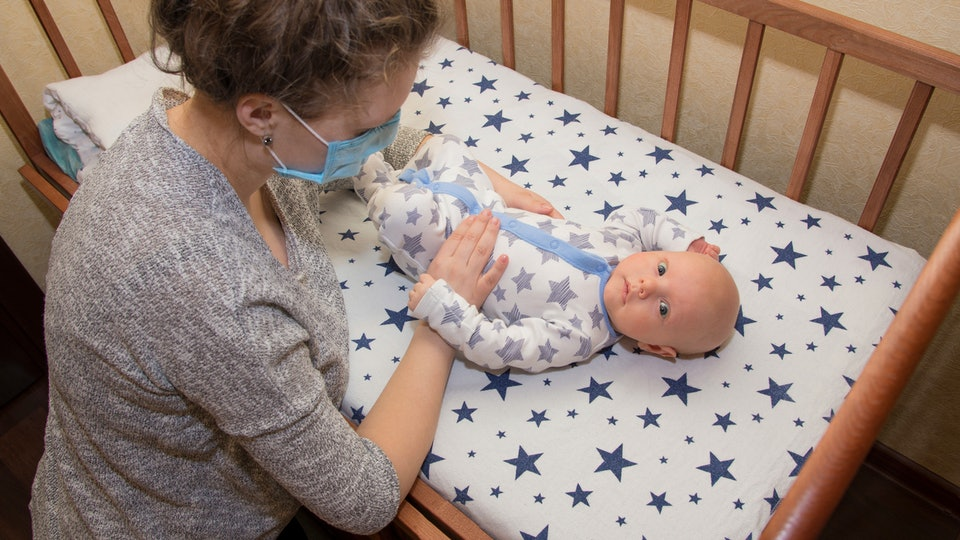 Mom wearing medical mask standing over baby in crib
