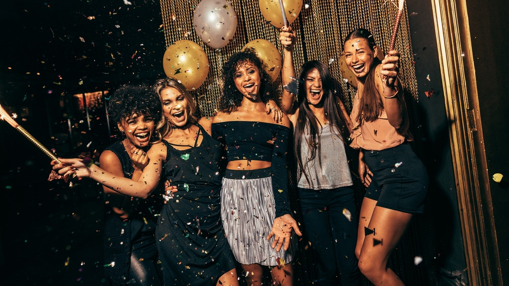 A group of girls laugh and pose in front of a gold backdrop at a club while confetti falls on New Year's Eve.
