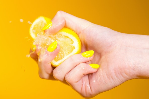 Lemon juice squirts out as hand with yellow fingernails crushes fruit