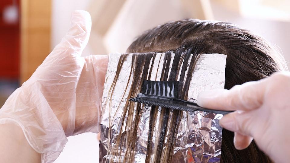 Process of dyeing hair at beauty salon, closeup