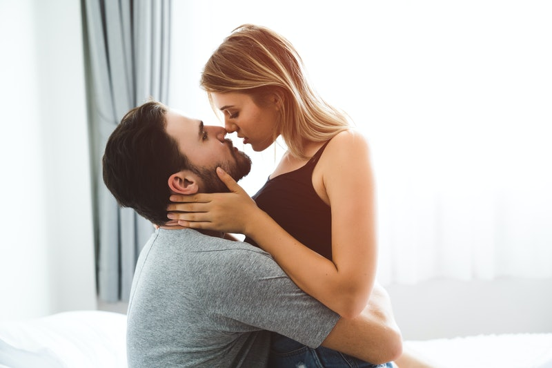 Cute couple relaxing on bed and kissing , love and relationships concept