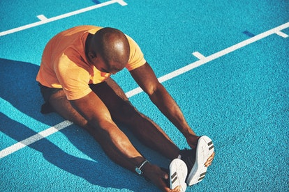 Focused young African male athlete in sportswear sitting alone on the lanes of a race track stretchi...