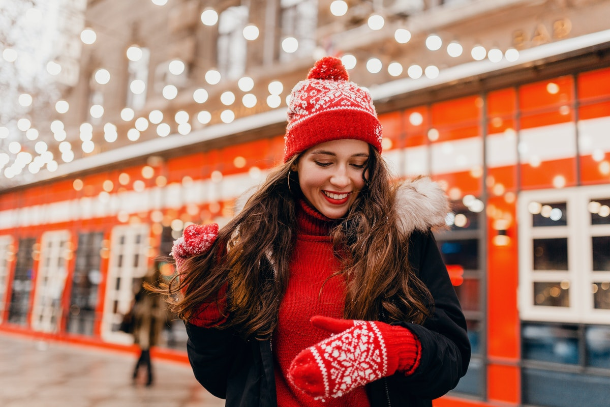young pretty smiling happy woman in red mittens and knitted hat wearing winter coat walking in city ...