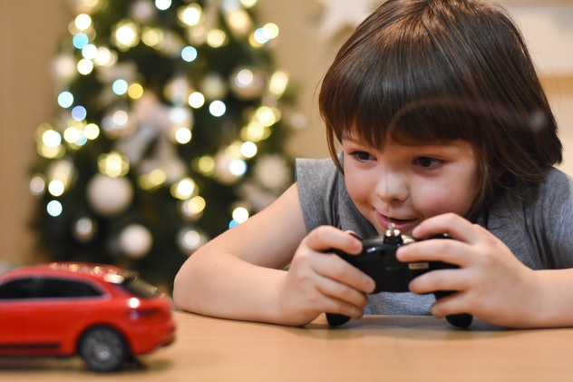 Happy boy play with car toys for Christmas. Smiling child having fun and playing with cars. Colorful lights on background