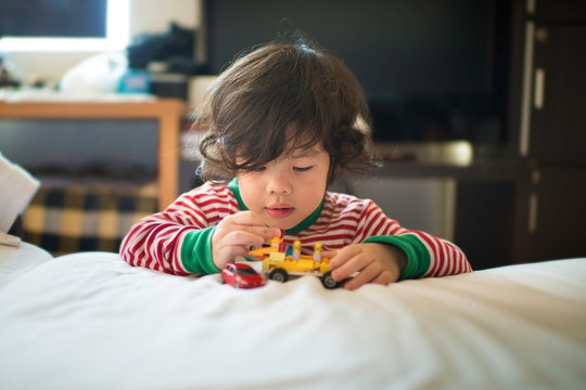 toddler boy playing with toys on Christmas morning
