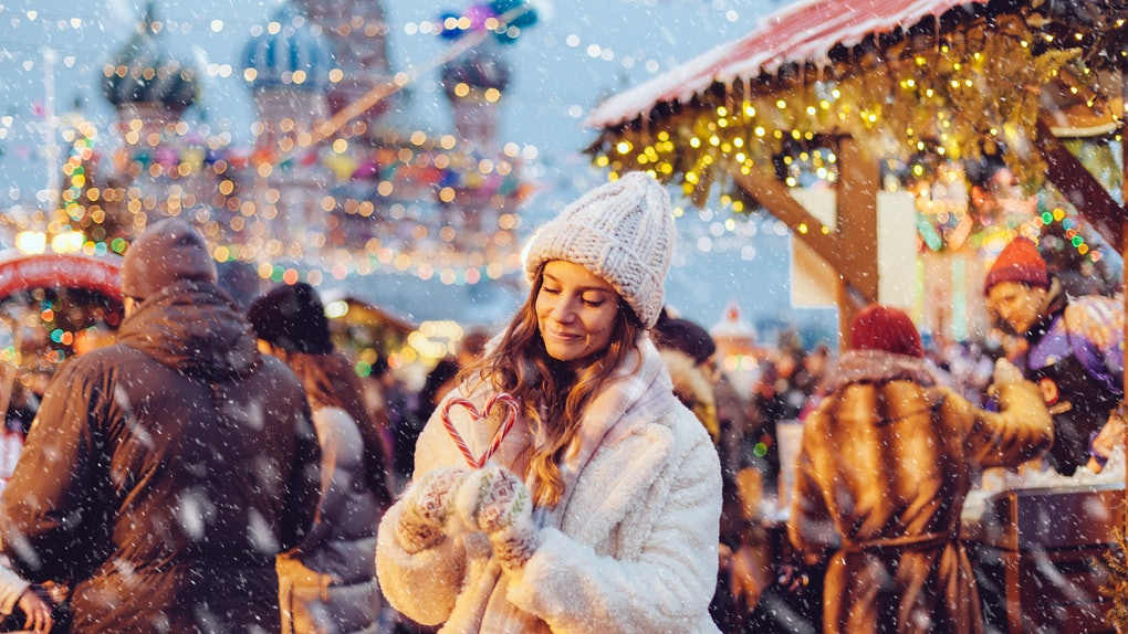 Girl walking in Christmas market decorated with holiday lights in the evening. Feeling happy in big city. Spending winter vacations in Red square, Moscow, Russia.