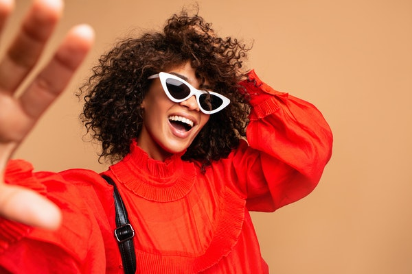 Portrait of beautiful young black woman taking selfie.Portrait of a pretty young afro american woman in retro style clothes smiling while standing and taking a selfie isolated over beige.