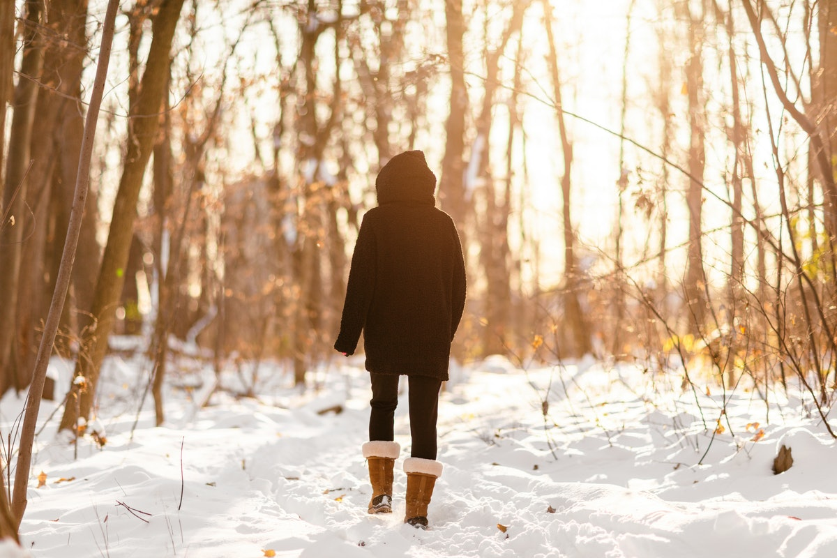 Winter snow walk woman walking away in snowy forest on woods trail outdoor lifestyle active people. Outside leisure.
