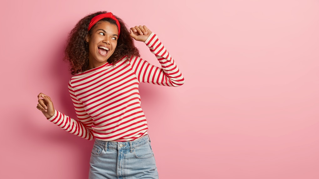 Active energized Afro woman dances and has fun, feels amused and upbeat, looks happily aside, performs victory dance, likes music rhythm, wears fashionable apparel, isolated on rosy studio wall
