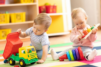 Kids playing with educational toys. Children sit on a rug in a play room at home or kindergarten. Toddler boy with toy lorry and baby girl with rings.