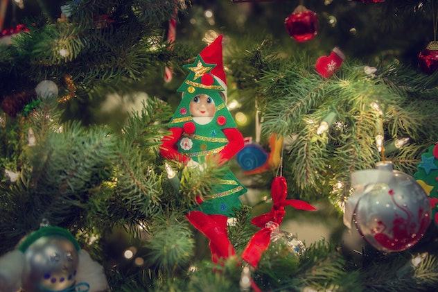 Elf on the shelf hiding in a tree.