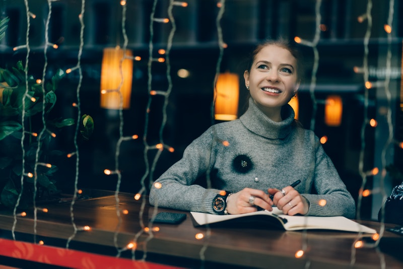 Young charming female smiling and looking outside window, writing Christmas wish-list and thinking o...