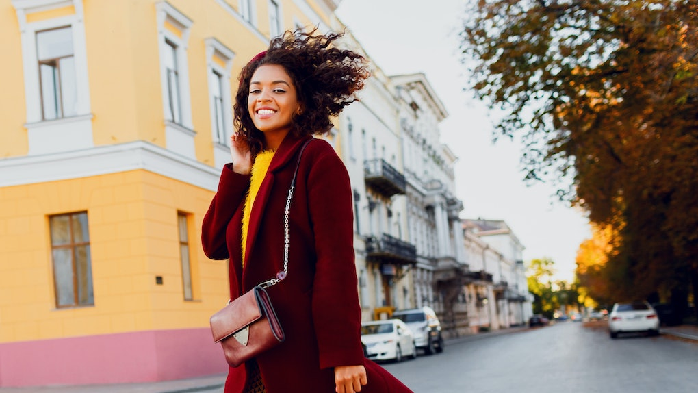 Smiling  black girl in amazing winter outfit and accessories posing on street  background. Wavy hairs. Fluffy sweater.