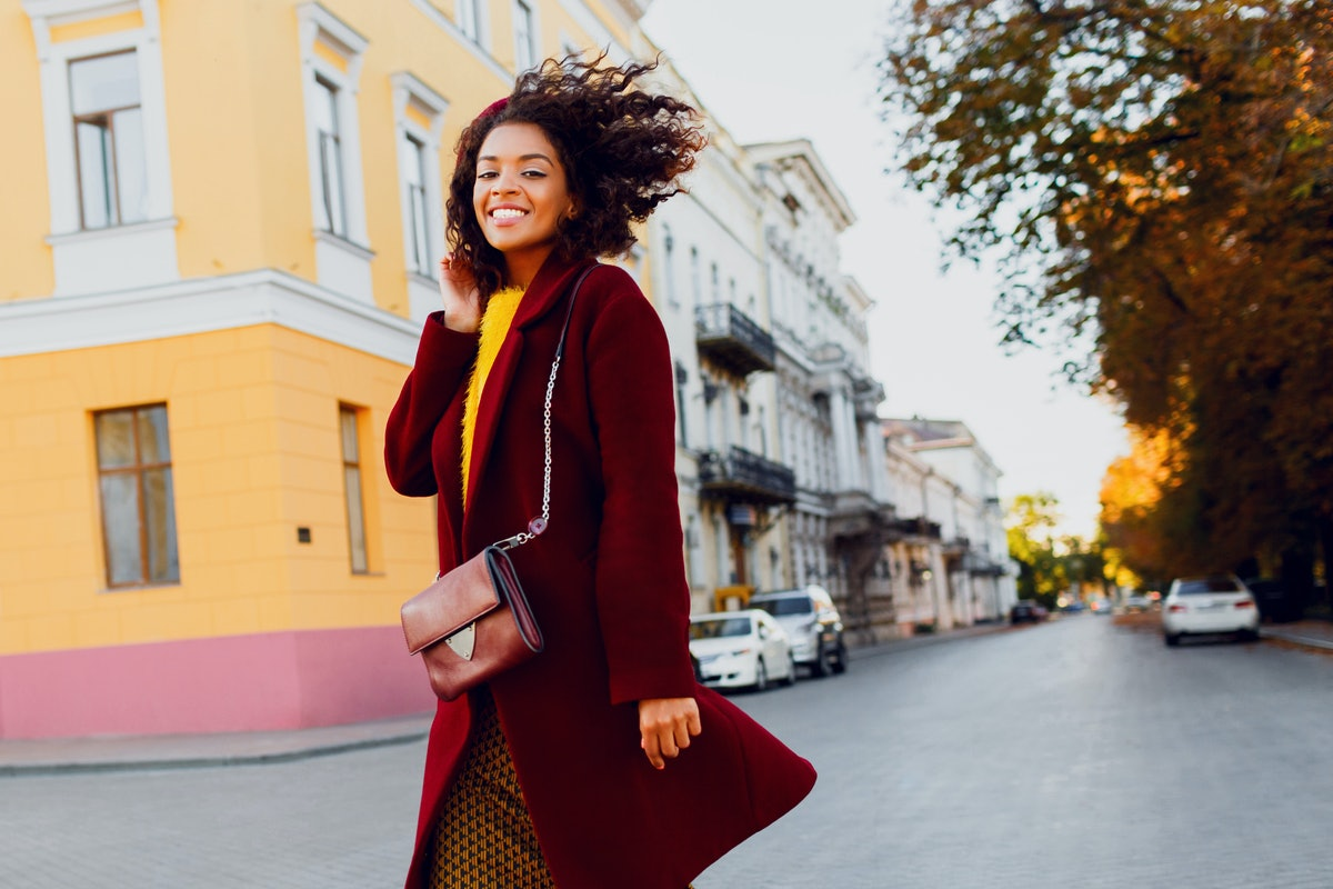 Smiling  black girl in amazing winter outfit and accessories posing on street  background. Wavy hair...