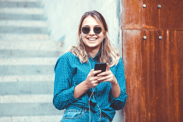 Portrait of a happy girl listening music on line with headphones from a smartphone in the street in a summer sunny day. Woman listening to music with the phone and having fun.