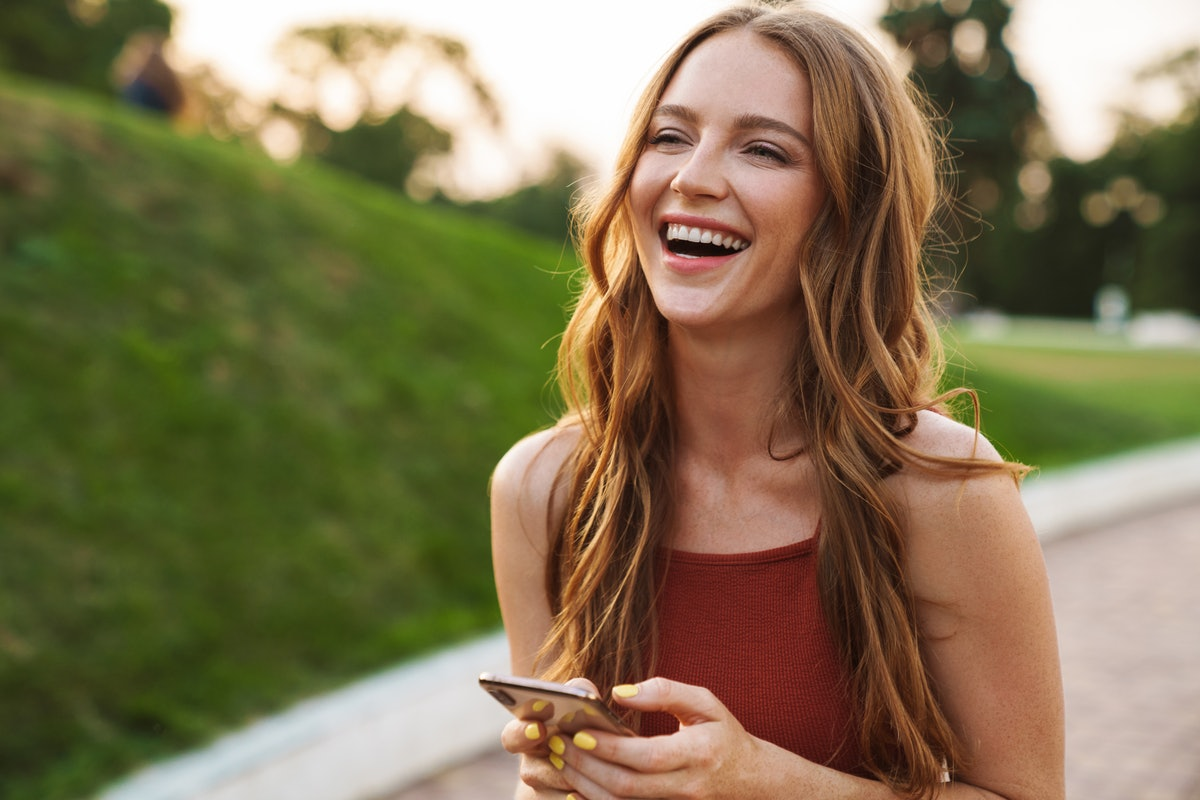 Photo of a happy laughing emotional young ginger woman walking in nature green park outdoors using m...