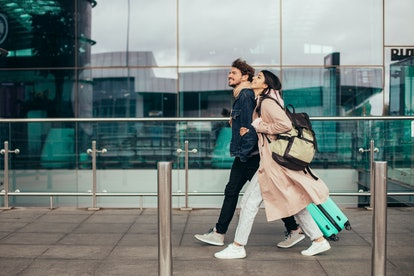 Young couple walking fast outside. In rush. Man and woman carry backpack and suitcase with clothes. Travel abroad. Trip or vacation. Picture little blurred. Vacation or honeymoon. In motion