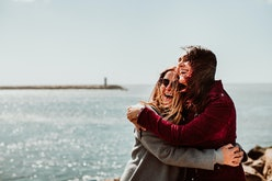 Lesbian couple laughing together on their trip to Porto in Portugal. Walking along the coast on a w...