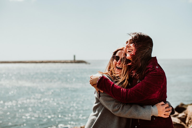 Lesbian couple laughing together on their trip to Porto in Portugal. Walking along the coast on a windy afternoon. Inclusive love. Lifestyle. Travel photography