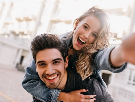 Curly adorable girl fooling around with boyfriend. Laughing graceful lady making selfie on street background.