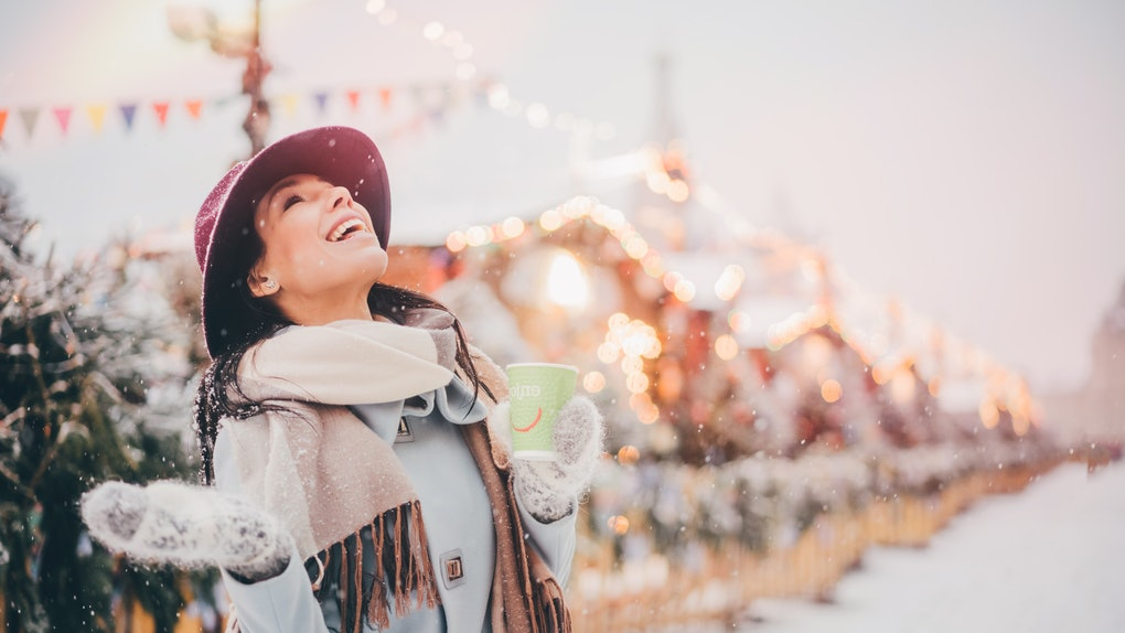 A happy woman stands in a snowy Connecticut Christmas town while holding a coffee mug and looking up at the snow falling.