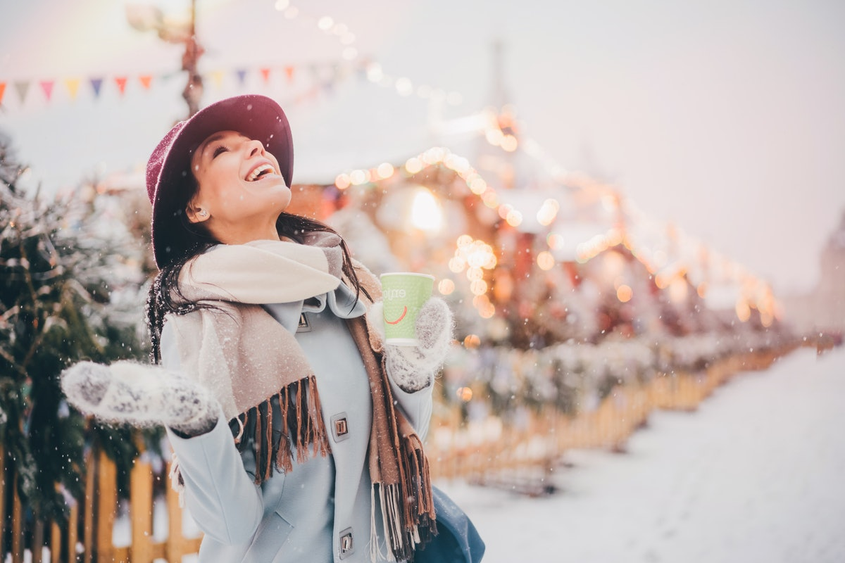 A happy woman stands in a snowy Connecticut Christmas town while holding a coffee mug and looking up...