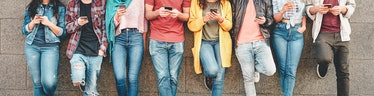 Group of friends using their smart mobile smartphones outdoor - Millennial young people addicted to ...