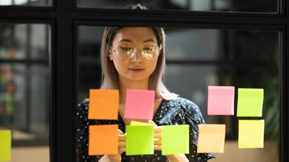 Serious focused young female coach teacher student asian business woman working on project strategy plan writing target tasks creative ideas on sticky post it notes on glass scrum board office wall