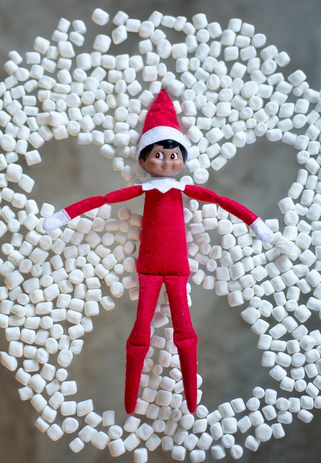 The elf on the shelf makes a snow angel from marshmallows. Elf in red suit and red hat