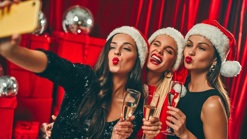 Happy New Year to you! Three beautiful sexy women in Santa hats with glasses of champagne take a selfie. New Year's party. Christmas Eve. Against the background of red gift boxes and disco balls.