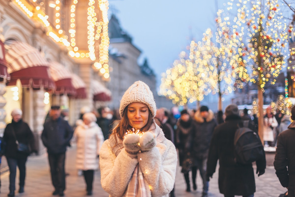 A woman wearing mittens, a sweater, and warm hat holds Christmas lights in the middle of a Connectic...