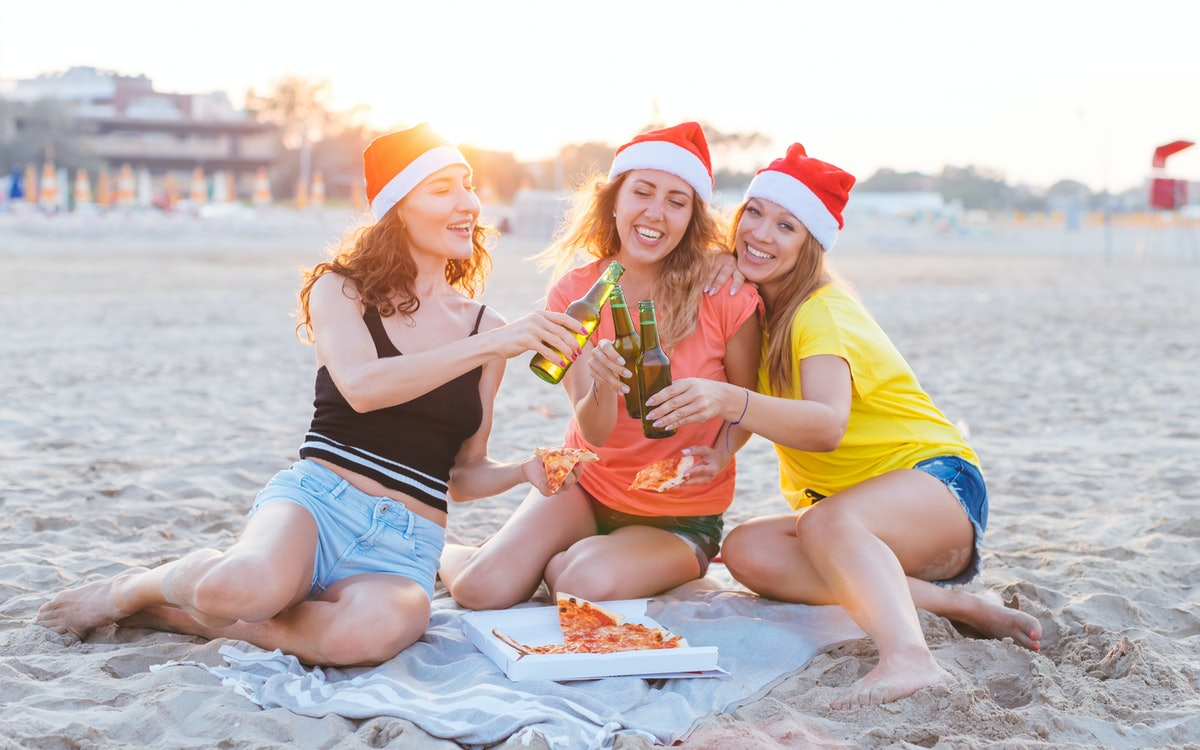 A group of friends cheers on the beach on a tropical Christmas vacation while wearing Santa hats and...