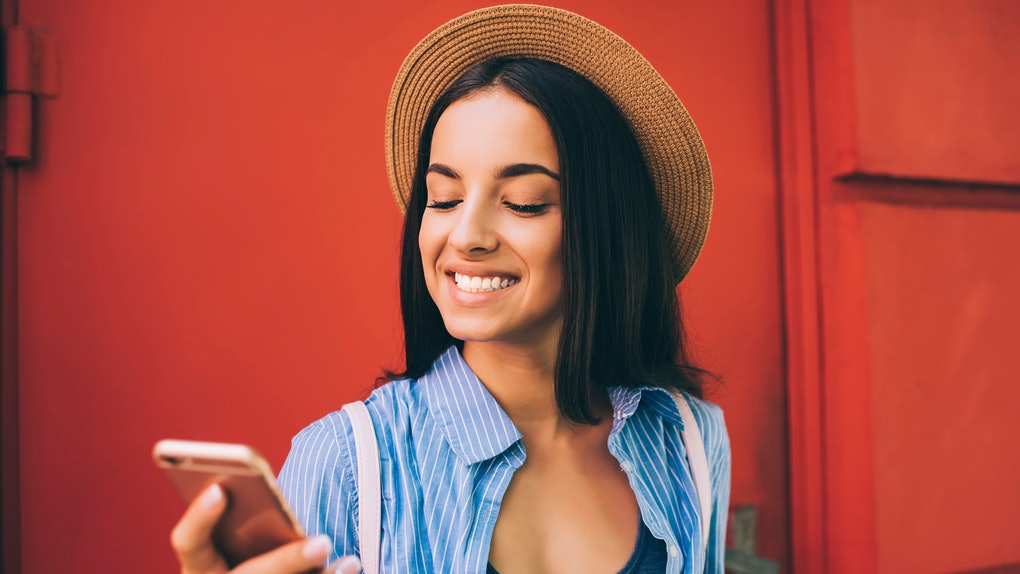 Cheerful Ukrainian woman laughing during online chatting with best friend connecting to 4g wireless for networking web pages, positive hipster girl using cellphone gadget for communicate outdoors