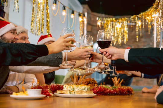 people toasting each other at a Christmas party over a table of food