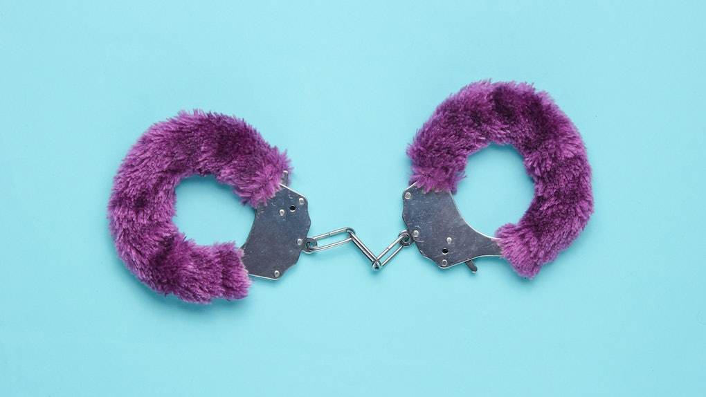 Handcuffs for sex games on blue background. Sexual bdsm toy. Love concept.